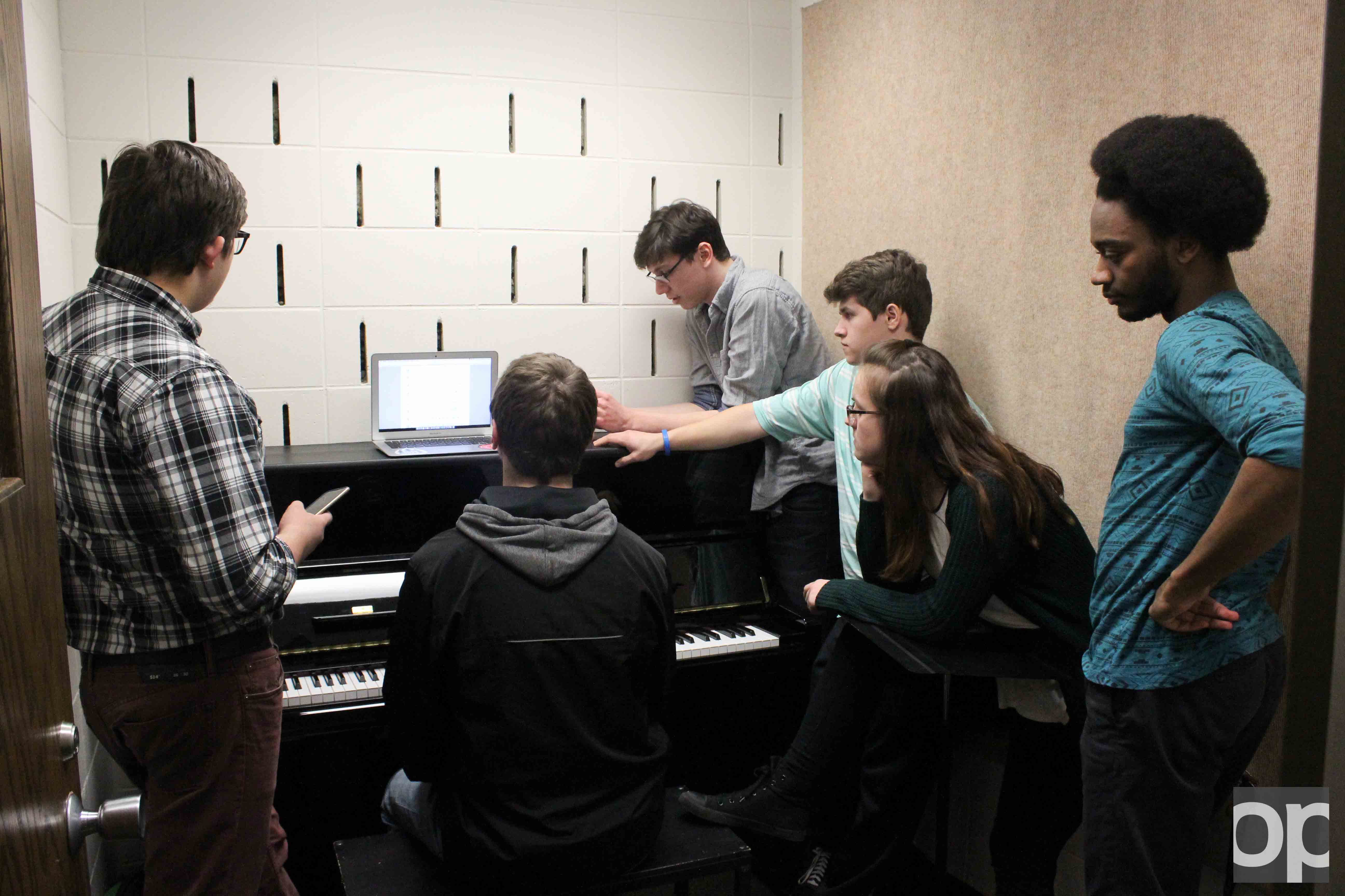 Members of a cappella group Gold Vibrations gather around to practice in Varner Hall.