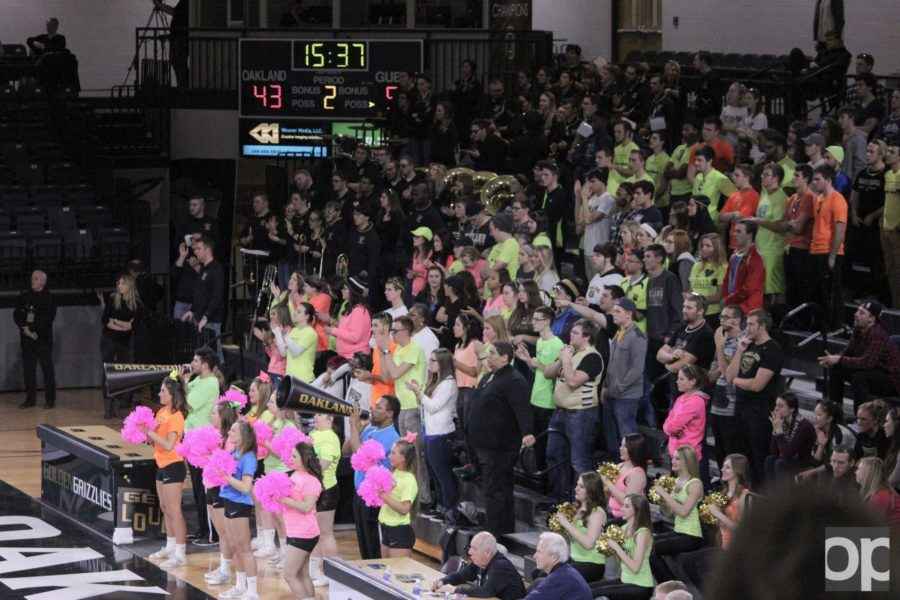Wearing neon colored outfits, the student section cheers on the mens basketball team. The mens team played in front of a crowd of 2,533 people in attendance.