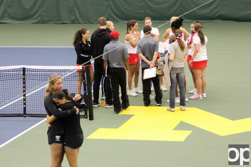 Golden Grizzlies Karine Celis and Maxime Colen embrace in front of a victorious Youngstown State team. Oakland lost 4-1.