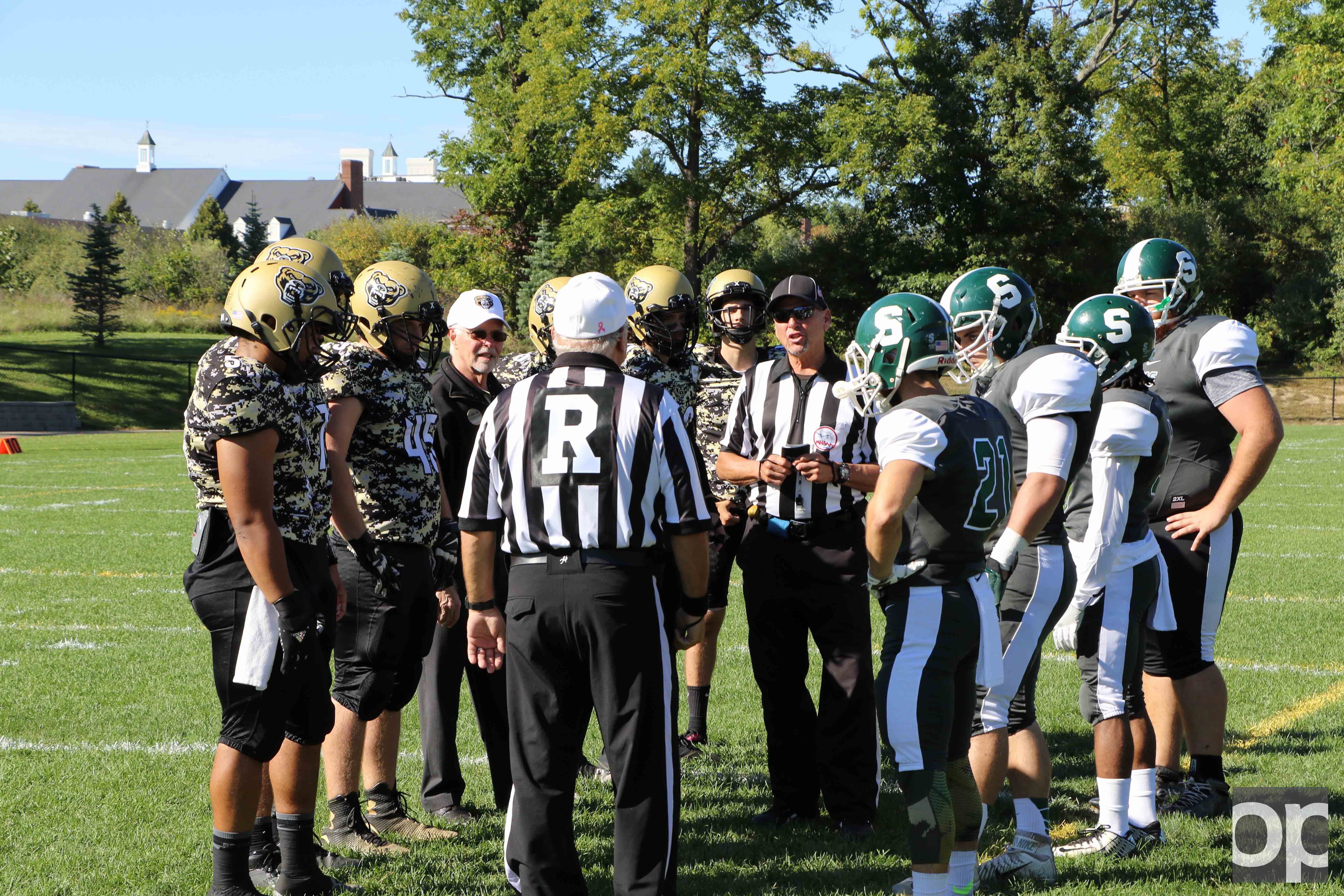Oakland University President George Hynd joins in on the coin toss decision before the beginning of the game.