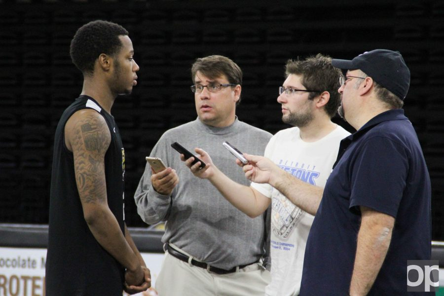 Men's basketball player Nick Daniels is interviewed by reporters on media day.