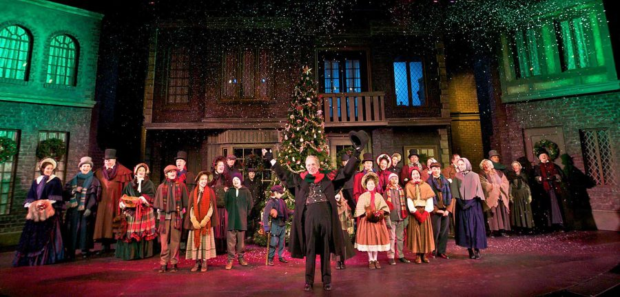 Thomas D. Mahard plays Scrooge on stage with the company of