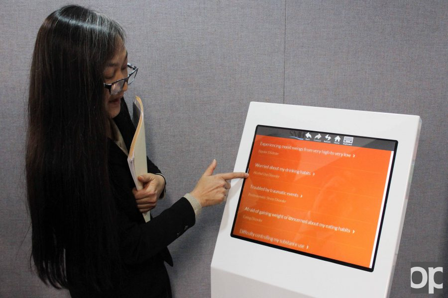Lakhana Peou, MSW, Director of Programs for Screening for Mental Health, displays the functions of the new MindKare kiosk in Kresge Library.