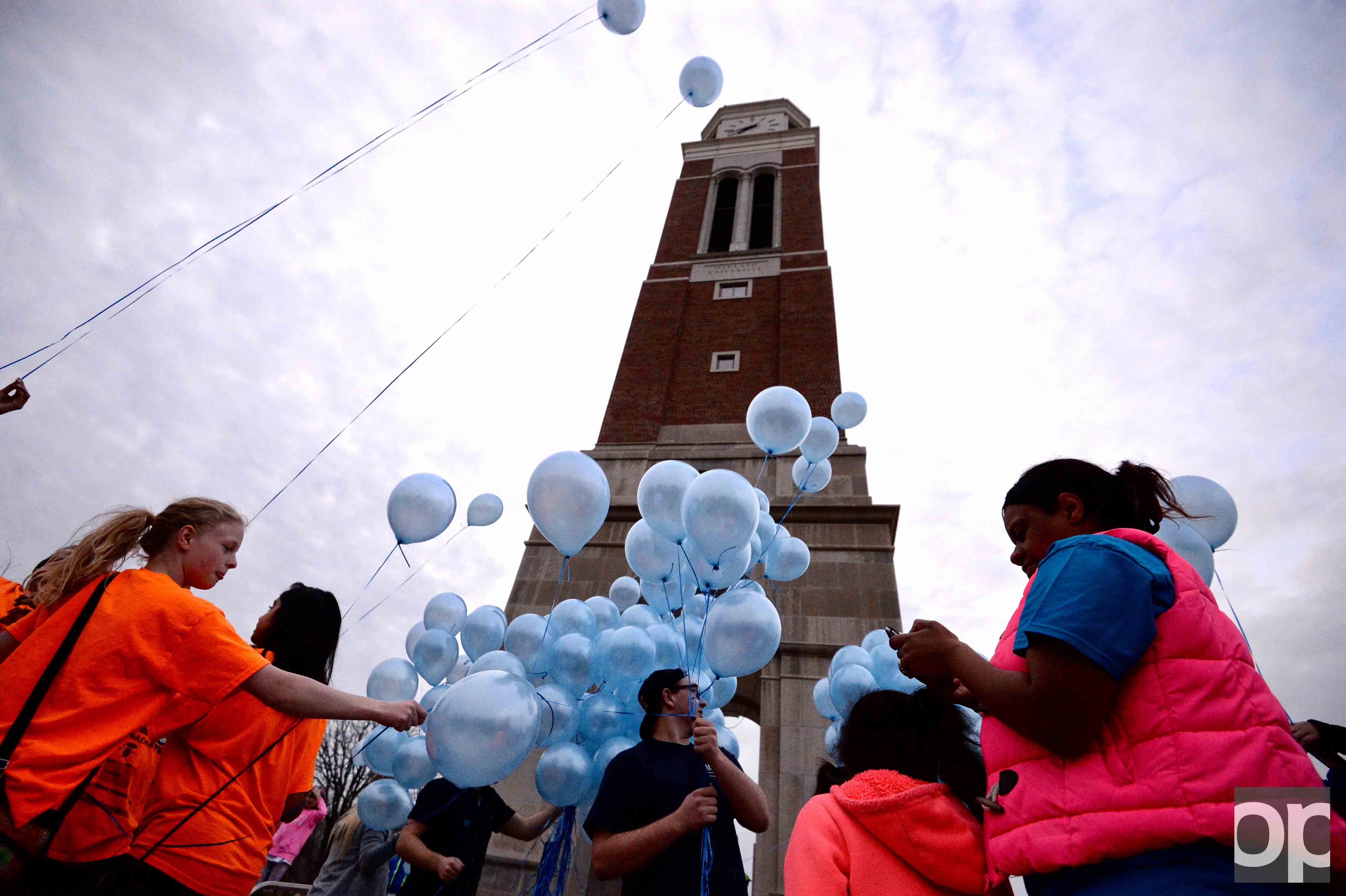 Participants gathered around the Elliott Tower with blue balloons on World Autism Awareness day.
