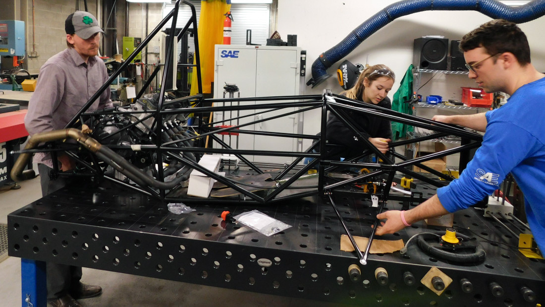 From left: Gavin McPherson, Bella Lane and Adam Delbeke work on the GRX9. Control arms have been added to the sides and the engine has exhaust pipes.