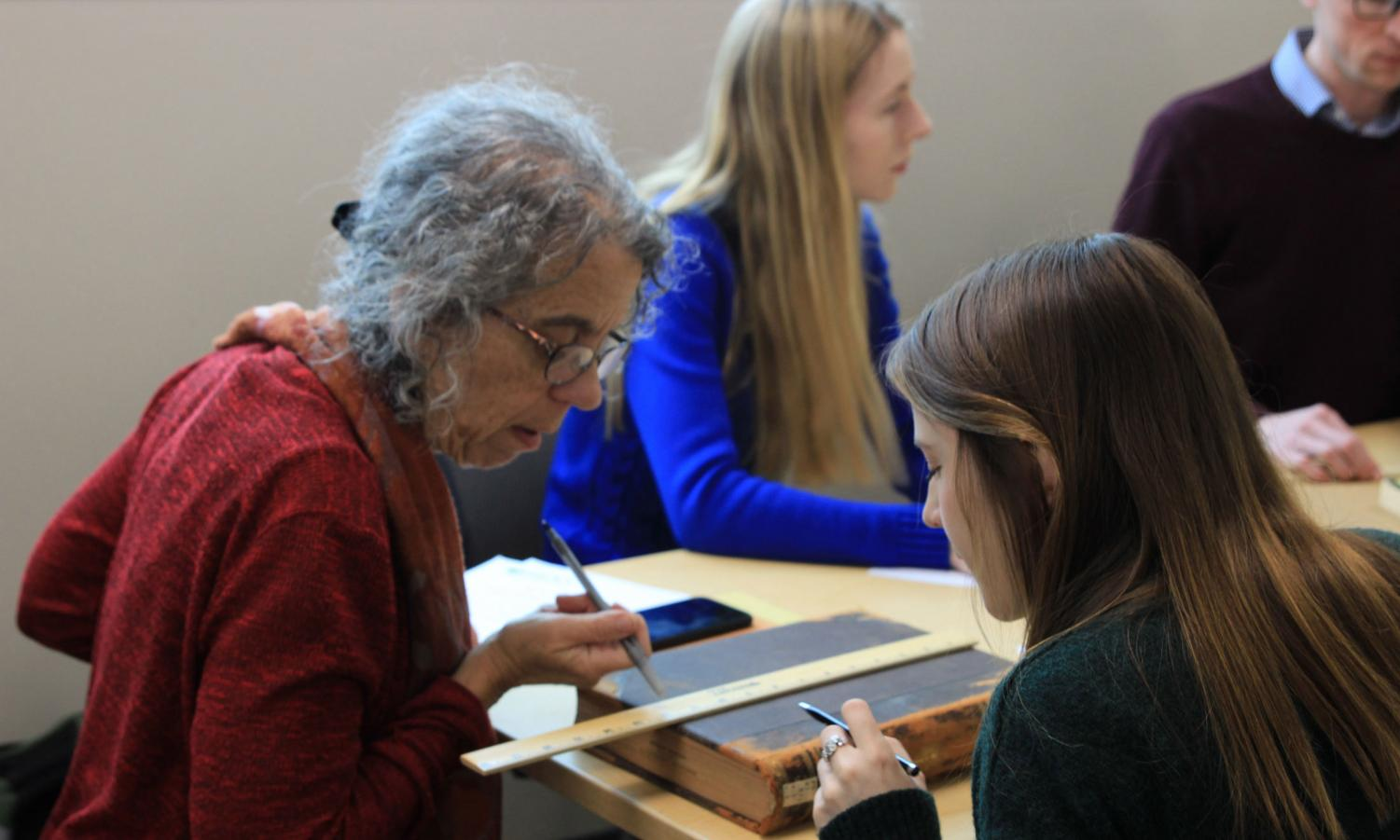 Students and staff participate in book measuring during a workshop on preserving old and rare books.