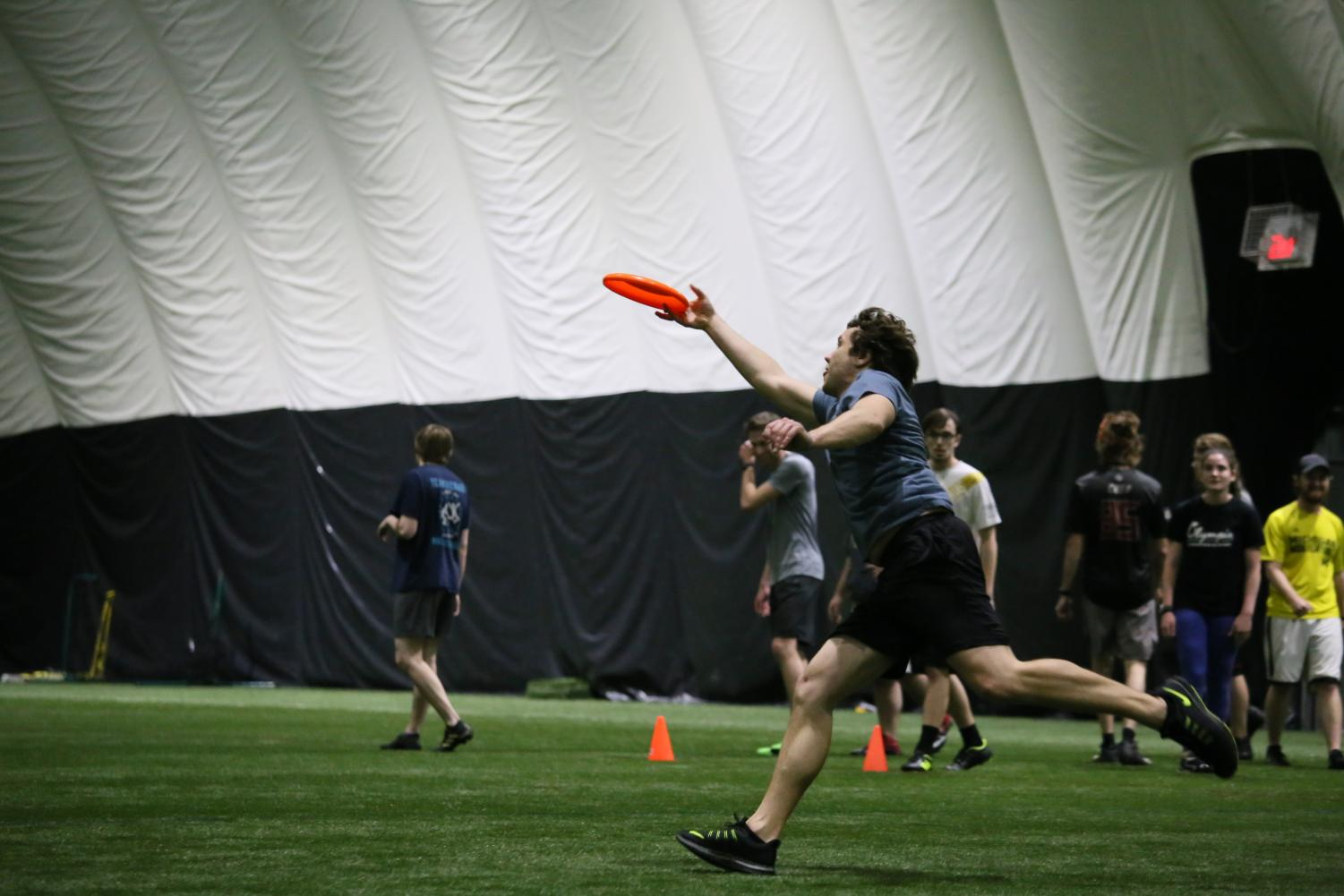 An Oakland Outlaw runs to catch the frisbee at a weekly practice on campus.