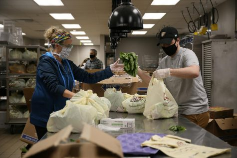 Two volunteers handle produce in the Oakland Center.