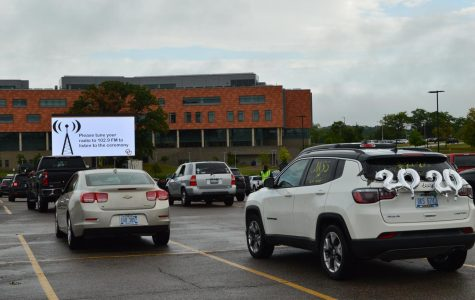 Many vehicles were decorated for graduation. All vehicles were facing toward a large screen, where all information and videos were shown.