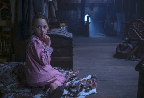 "Flora hides in the attic at Bly Manor with a ghostly presence. Amelie Bae Smith plays Flora in Netflix's ""The Haunting of Bly Manor."""