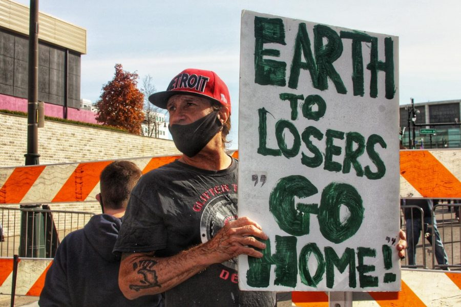 "Counter protester Scott Koskinen, 55, of Detroit, carries a sign that said, ""Earth to losers: Go home."" Photo by Rachel Basela."