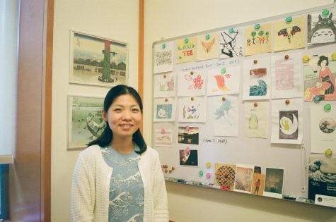 Nozomi Naoi stands next to some of her art collection.