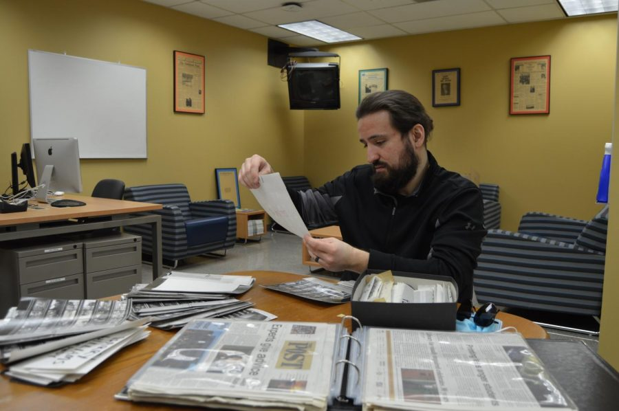 """Horatiu Zglimbea sorts through the Oakland Post's photo archives to add to """"Oakland through the decades."""" This is an ongoing project he's working on to inform more people about OU's history."""