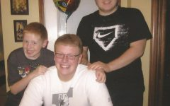 At his childhood home in Capac, MI, Jeff Thomas takes a break from his birthday celebration to pose with his two younger brothers.