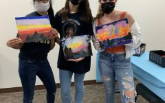 """HOMES hosted a painting event called """"Destress with Bob Ross"""" in the  Oakland Center in April to relax before finals. Eboard members Pooja Patel, Hannah Brendle and Meghan Savel proudly display their artwork."""