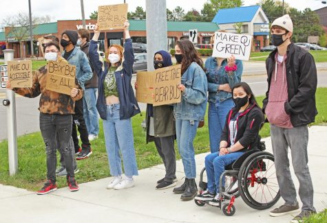 Students hold their signs out toward traffic at the OUSWC organized protest to bring back the Bear Bus on May 5.
