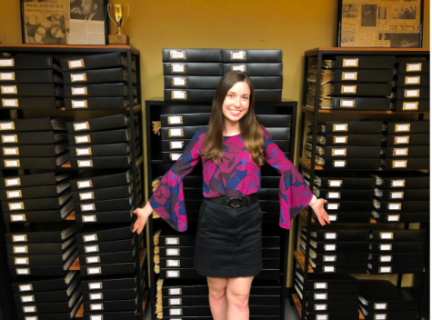 Emily Morris strikes a pose in front of the archives she spent the 2020-21 school year organizing. Thanks to her hard work, The Oakland Post archives are now accessible to the campus community.