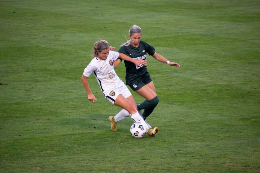 Midfielder+Macey+Wierenga+trying+to+slip+a+defender+against+Michigan+State+on+Thursday%2C+Sept.+9%2C+2021.+