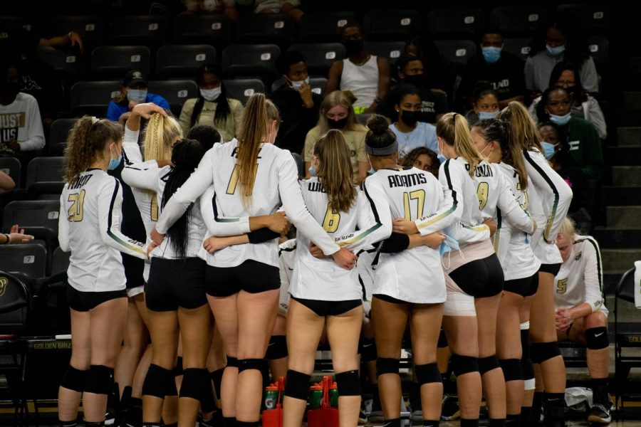 The Volleyball team in a huddle during a timeout.