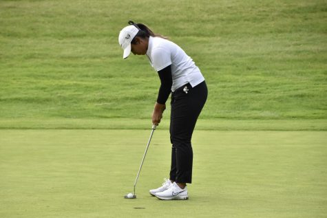 A member of Oakland Universitys womens golf team lines up for a putt on Monday, Sept. 27.