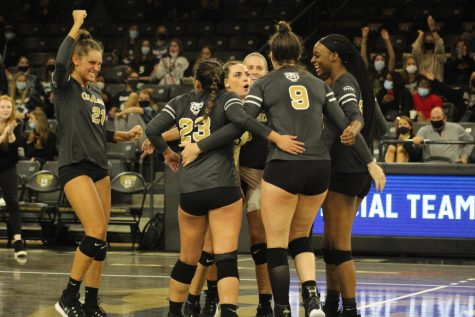 The volleyball team celebrates after getting a point against UIC on Oct. 8.